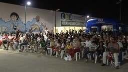 Moradores assistem filme ao ar livre no Bairro Cidade Vera Cruz, em Aparecida de Goiânia