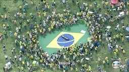 Manifestantes estendem bandeira brasileira na Esplanada dos Ministérios