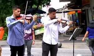 Violinistas tocam 'Titanic' em frente ao prédio de Cabral e ganham fama