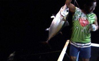 Tripulação de barco aproveita para pescar à noite - Toda ação acontece à noite, porque as luzes do barco atraem o cardume de peixes voadores para o entorno da embarcação. O peixe voador é utilizado como isca para pegar o atum.