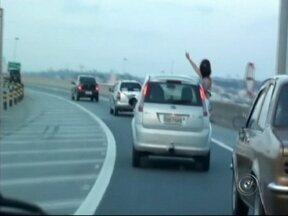 Mulher é flagrada sentada em janela de carro em rodovias de Jundiaí, SP - Um cinegrafista amador registrou neste domingo (23) uma mulher sentada na janela de um carro, em Jundiaí (SP). Nas imagens, a mulher acena para outros motoristas com o corpo para fora do veículo.