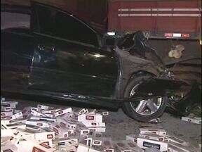 Carro com cigarro contrabandeado se envolve em acidente no Noroeste - O motorista abandonou a passageira presa nas ferragens e fugiu. A carga ficou espalhada na pista.