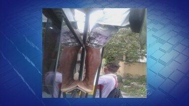 Passageiros se arriscam no transporte coletivo de ManaUS - Imagem mostra passageiro sendo transportado pendurado na porta do ônibus da linha 458.