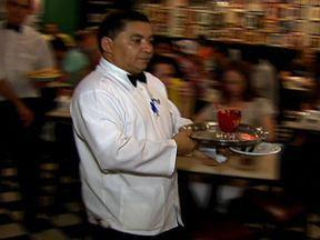 Atendimento ao cliente é uma das especialidades de São Paulo - Os garçons de uma churrascaria recebem treinamento especial. Em um shopping, atendentes ajudam clientes a encontrarem lojas e outros.