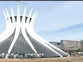 Turistas e arquitetos dão abraço simbólico na Catedral de Brasília - Durante dez minutos, cerca de 70 pessoas protestavam contra os atos de vandalismo ao prédio depredado durante a manifestação da última quinta-feira (20). O Palácio do Itamaraty também recebeu um abraço simbólico de funcionários e turistas.