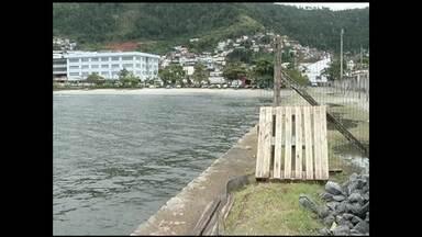 Depois de cinco meses interditado, Cais de Angra dos Reis, RJ, começa a ser reformado - Três mergulhadores fazem o reparo no muro de pedra.