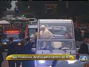 Papa Francisco beija criança na Avenida Rio Branco (RJ) - Durante o percurso pelo Centro do Rio, o pontífice acena para os fiéis e beija crianças. O Papa Francisco usa uma batina branca.