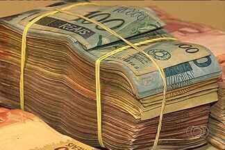 PF identifica 4 suspeitos de ligação com R$ 1,3 milhão achado em carro em Goiânia - A suspeita é de que parte do dinheiro tenha sido sacado em uma agência da Caixa Econômica Federal, na capital. Alguns pacotes continham a identificação do banco.