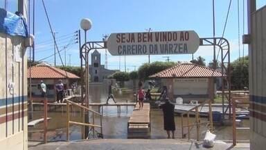 Cheia causa alagações em bairros do Careiro da Várzea, no AM - Orla da cidade foi tomada pela água do rio; pontes foram construídas para permitir tráfego de pessoas.