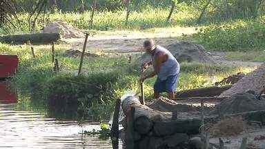 Moradores que dependem da pesca no Rio Novo aprendem a viver outra realidade - Com a escassez do peixe, famílias sobrevivem da extração de areia.