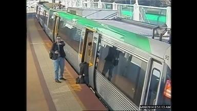 Passageiro fica preso em vão de trem na Austrália - O rapaz coloca a perna direita no vagão e a esquerda cai no vão entre a plataforma e o trem. O passageiro que está atrás vê e rapidamente chama socorro.