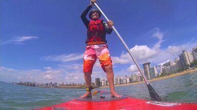 Aos 78 anos, frei pratica 'stand up paddle' em praias do ES - Ele conta que atividade desenvolvida prédio no local ajuda no preparo físico.