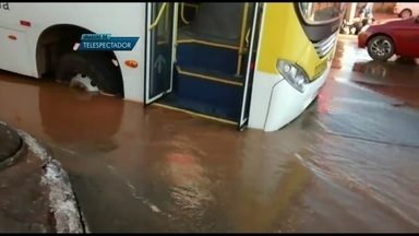 Ônibus fica preso em buraco numa rua de São Sebastião - O pneu da frente do ônibus ficou preso no buraco. A rua ficou alagada por causa de um vazamento de água, que cobriu a cratera, na avenida da Gameleira.