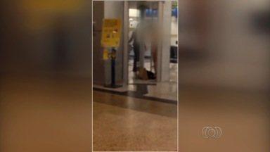 Mulher tira roupa após não conseguir entrar em banco, em Goiânia - Porta giratória do estabelecimento travou enquanto a consumidora passava.Agência suspeita que havia metal no sapato da moça que tentava entrar.