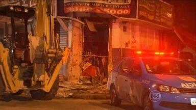 Bandidos usam retroescavadeira para roubar caixa eletrônico no RJ - Ladrões usaram a máquina para quebrar a parede de uma farmácia. A polícia recuperou o cofre do equipamento e um homem foi preso.