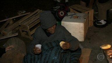 Voluntários distribuem alimento e bebida quente a moradores de rua na Praça da Sé - A temperatura mínima na capital ficou em 6,8ºC na madrugada. A sensação é de mais frio para as 16 mil pessoas que moram nas ruas na capital, que recorrem a fogueiras e até a papelão para se aquecer.