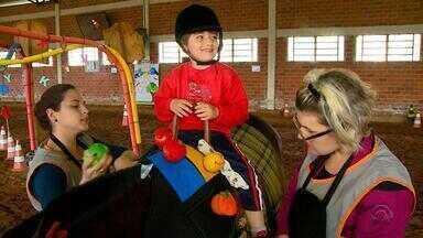 Equoterapia pode ajudar pacientes que sofrem com problemas motores - Crianças autistas e com microcefalia têm apostado no tratamento com cavalos.