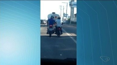 Motociclista trafega com o pé e a mão na moto do lado, no ES - Ele pode ser multado por rebocar moto e por dirigir sem a devida intenção e cuidados com a segurança.