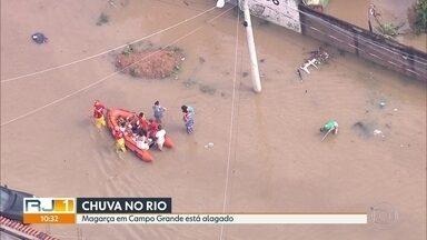 Moradores são resgatados em botes em Campo Grande - Rio Cabuçu transbordou, inundando a região. Casas e ruas do Jardim Maravilha, no Magarça, em Campo Grande, estão alagadas. Crianças brincam na enchente.