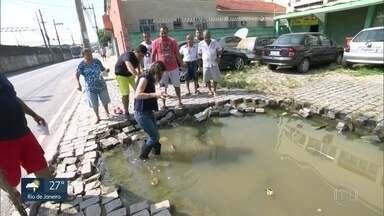Blitz do RJ Móvel: moradores de Cascadura enfrentam obstáculos da chuva - Tem crateras formadas pela chuva, com água de esgoto. Fio caído representa mais um risco. Entulho está no meio da rua.