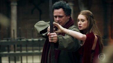 Amália dá aulas de arco e flecha para Gregório - O conselheiro de Afonso fica perturbado com a proximidade da ruiva