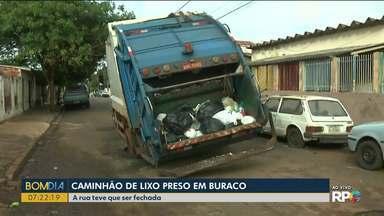 Caminhão de lixo fica preso em buraco de rua - O asfalto cedeu em um ponto onde passa uma rede de água.