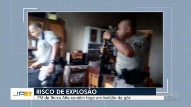Polciais combatem incêndio usando mangueira, em Barro Alto - Eles acabaram com as chamas antes da chegada do Corpo de Bombeiros.