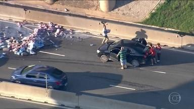 Caminhão com leite sofre acidente na Fernão Dias e carga é saqueada - Acidente envolveu outro caminhão e um carro. Muitas pessoas que passagem de carro, moto e bicicleta pararam para levar leite.