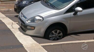 Asfalto cedeu enquanto motorista aguardava em semáforo - De acordo com o motorista, ele parou em um semáforo da capital quando o asfalto cedeu e o carro ficou preso no buraco que se formou.