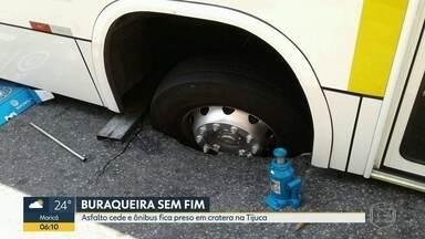 Asfalto cede e ônibus fica preso em cratera na Tijuca - O veículo estava parado quando o asfalto cedeu acabou deixando o ônibus preso.