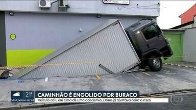 Caminhão é engolido por buraco e cai em cima de academia - Dono da academia já tinha avisado ao supermercado e à imobiliária das trepidações quando os caminhões estacionavam no local.