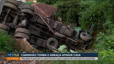 Caminhão tomba e ameaça atingir casa em Curitiba; motorista ficou preso nas ferragens - Em outro acidente, mulher foi atropelada no quintal da casa dela enquanto estendia roupa.