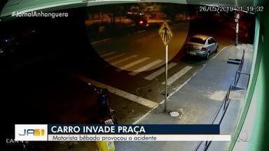 Carro quase atinge mulher em faixa de pedestre, 'voa' sobre calçada e capota em praça - Bafômetro apontou que motorista estava bêbado e ele foi preso. Foram encontradas latas de cerveja no carro.
