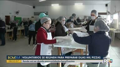 Voluntários se reúnem para preparar duas mil pizzas - Renda vai ser doada para entidades beneficentes.