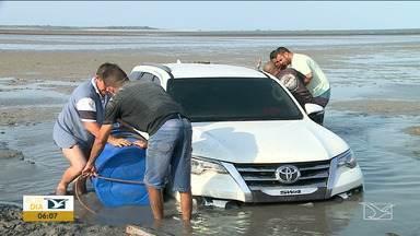 Quase 48 horas depois, veículo continua atolado em praia em São José de Ribamar - Carro de passeio continua atolado na Praia de Panaquatira, apesar das tentativas de resgate.