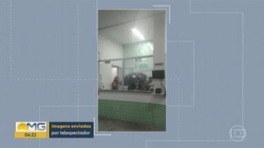 Servidores usam guarda-chuva dentro da UPA de Contagem durante temporal - Recepção estava com goteiras.