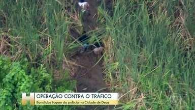 Suspeitos deitam na lama para fugir da PM, na Cidade de Deus, zona oeste do Rio - Ninguém foi preso. Operação da PM era contra tráfico de drogas e derrubou barricadas.
