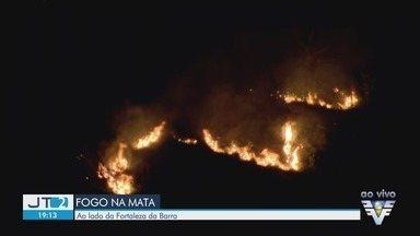 Fogo atinge mata ao lado da Fortaleza da Barra em Guarujá (SP) - Câmera ao vivo mostra incêndio. Não há informações sobre o que causou as chamas.