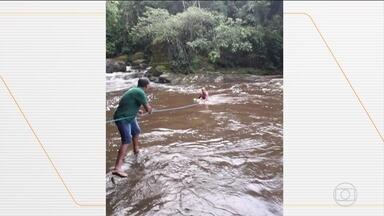 Depois de cabeça d'água, três banhistas são resgatados em Guapimirim (RJ) - Segundo a prefeitura, eles eram turistas e ignoraram os alertas para sair da cachoeira. Moradores da região usaram cordas para salvar os banhistas.
