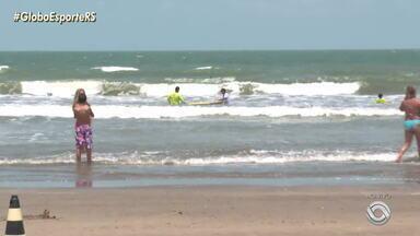 Na praia do Cassino, em Rio Grande, veranistas praticam aulas de surfe na beira-mar - Assista ao vídeo.