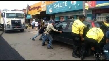 Homens carregam carro que entrou em local proibído em Aparecida de Goiânia - Fiscais não encontraram motorista e se uniram para retirar o veículo que estava em local que teria asfalto refeito.