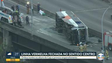 Ônibus tomba na Linha Vermelha e provoca congestionamento - Equipes da Prefeitura e do Corpo de Bombeiros tentam retirar o veículo da pista sentido centro, na altura do Caju.