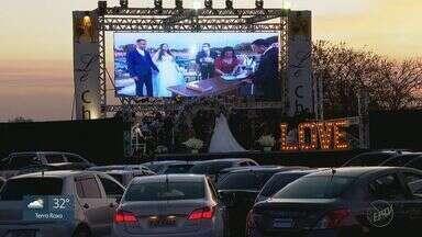 Noivos ganham 'casamento drive-in' após adiarem sonho por causa da pandemia - Cerimônia organizada por amigos e familiares foi transmitida por telão e padrinhos formaram corredor de carros para entrada do casal.