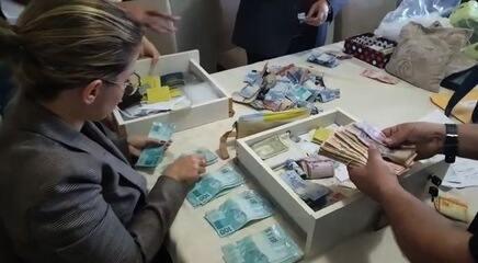Investigadores contam dinheiro apreendido em fundo falso de guarda-roupa de vigário, em GO