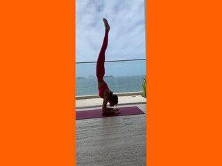 Adriana Camargo demonstra uma postura invertida de yoga: respiração, controle e oxigenação cerebral