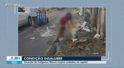 Criança indígena é vista tomando banho em água da rua em Belém.