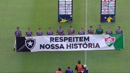 Jogadores do Fluminense entram em campo com faixa de protesto contra a volta do Cariocão