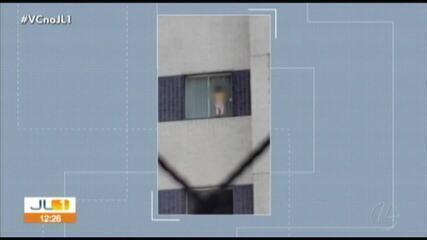 Criança é vista sozinha em janela de edifício em Belém