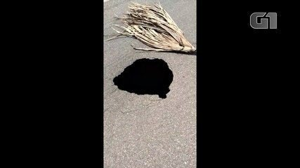 Morador mostra cratera no meio do asfalto na TO-455