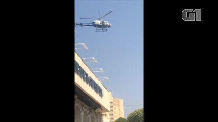 Helicóptero do Ciopaer sobrevoa colégio com a bandeira do Brasil em Cuiabá